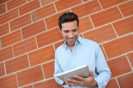 leant: Attractive man using electronic tablet leant on brickwall