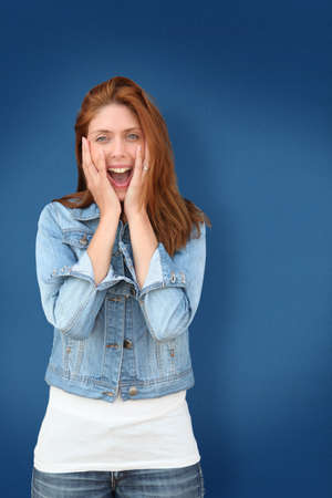 Woman on blue backgroudn with amazed look Stock Photo - 9479185