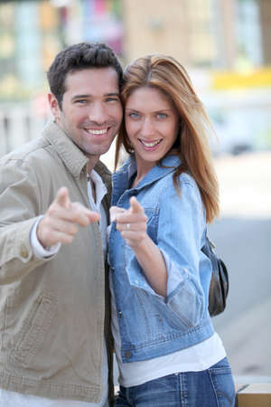 Happy couple with thumbs up in town Stock Photo - 9480169
