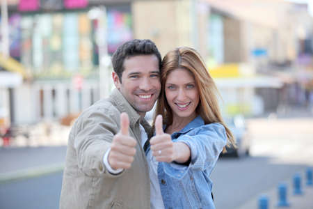 Happy couple with thumbs up in town Stock Photo - 9479522