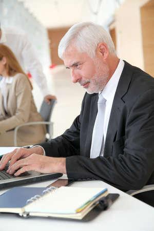 Senior businessman working on laptop computer Stock Photo - 9480601
