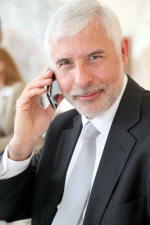 Portrait of senior businessman talking on the phone photo