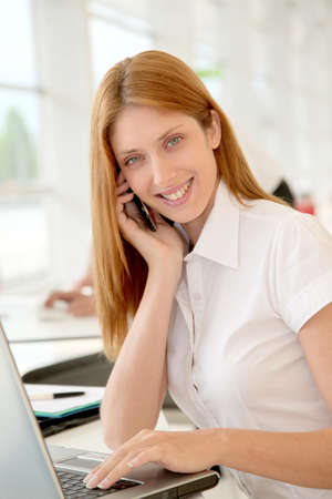 Smiling office worker in front of computer photo