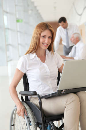 Businesswoman in wheelchair at work photo