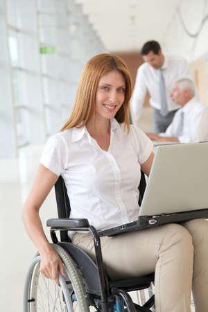 paraplegic: Businesswoman in wheelchair at work Stock Photo