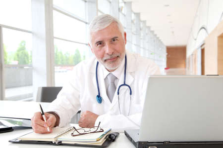 doctor laptop: Portrait of senior doctor in office