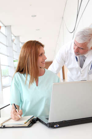 Doctor and intern working in hospital photo