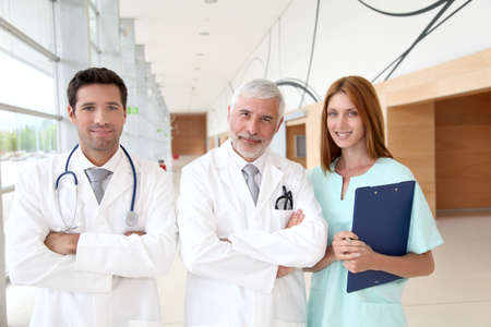 Portrait of medical team standing in hospital hall photo