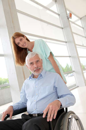 Nurse helping senior man in wheelchair photo