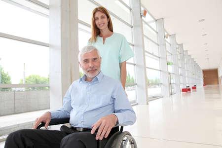 paraplegic: Amamantar ayuda a senior hombre en silla de ruedas Foto de archivo