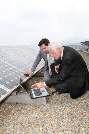 Businessmen checking solar panels running photo