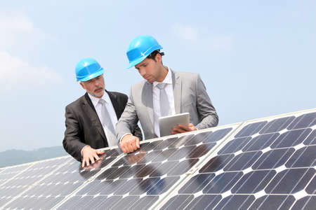 energia solar: Ingenieros de comprobaci�n de la instalaci�n de paneles solares Foto de archivo