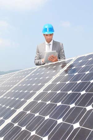 Businessman standing on solar panel installation Stock Photo - 9480774