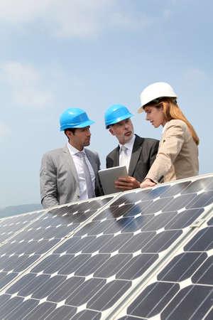 touchscreen: Ingenieros de comprobaci�n de la instalaci�n de paneles solares Foto de archivo