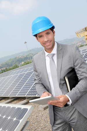 Businessman standing on solar panel installation Stock Photo - 9480818