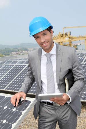 Businessman standing on solar panel installation Stock Photo - 9480806