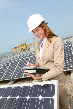 Woman engineer checking solar panels setup photo