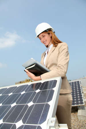 Woman engineer checking solar panels setup photo