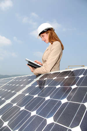 electric cell: Woman engineer checking solar panels setup