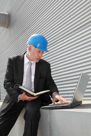 Site manager checking planning on computer photo
