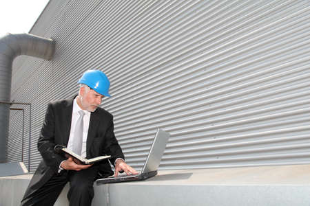 Site manager checking planning on computer Stock Photo - 9480760