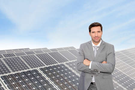 Businessman standing by photovoltaic installation photo
