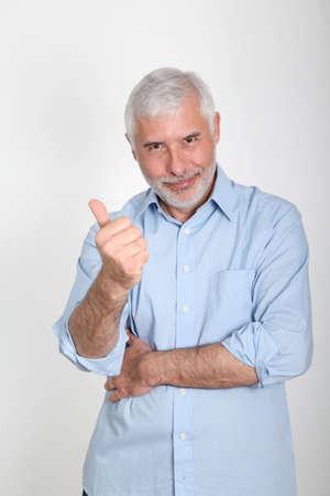 Portrait of smiling senior man wih thumb up photo