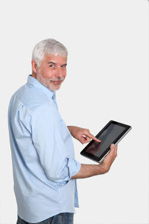 android tablet: Senior man using electronic tablet Stock Photo