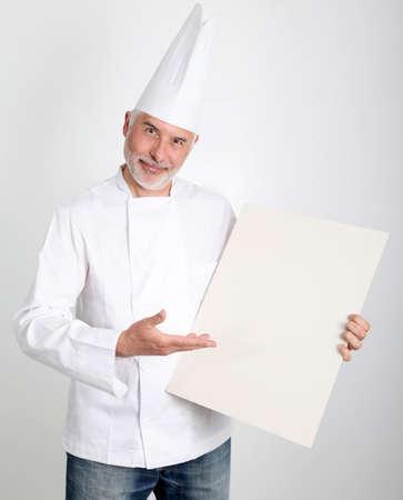 Smiling chef showing restaurant menu photo