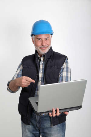 Construction worker using laptop computer photo