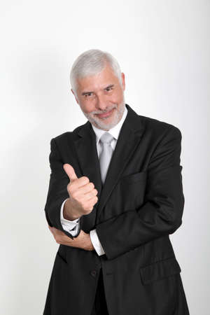 Portrait of senior businessman showing thumbs up photo