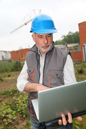 site manager: Site manager with laptop computer checking construction Stock Photo