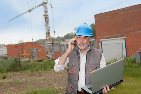 Construction manager on building site with laptop computer photo