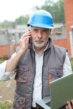 Construction manager on building site with laptop computer Banco de Imagens