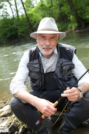 Portrait of fisherman sitting by a river Stock Photo - 9634898