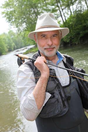waders: Retrato de pescador sonriente en riverside