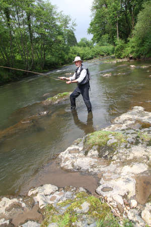 waders: Man fishing trout in river
