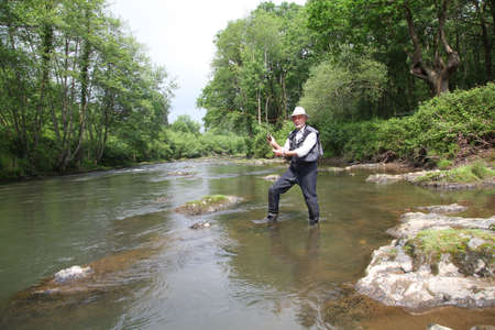 trout fishing: Man fishing trout in river
