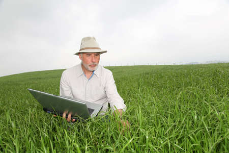 Farmer examining crop with laptop computer photo