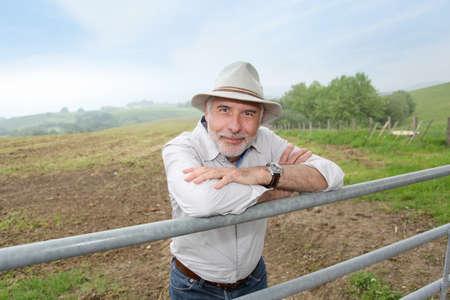 Farmer leaning on farmland fence  photo