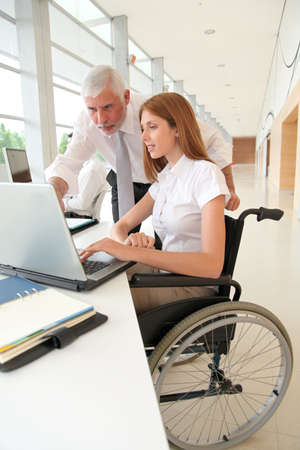 Woman in wheelchair with trainer in office Stock Photo - 9784544