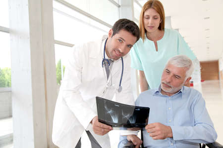 Medical team checking X-ray with patient photo