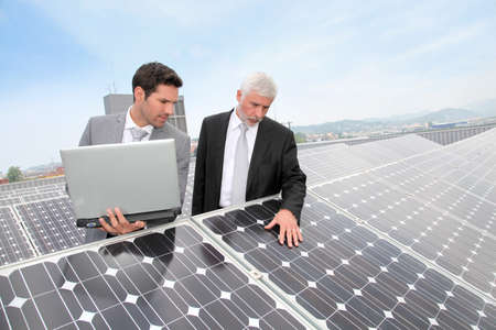 Business people standing by solar panels photo