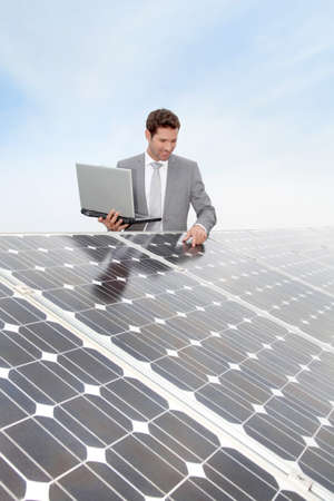 Businessman standing by solar panels photo