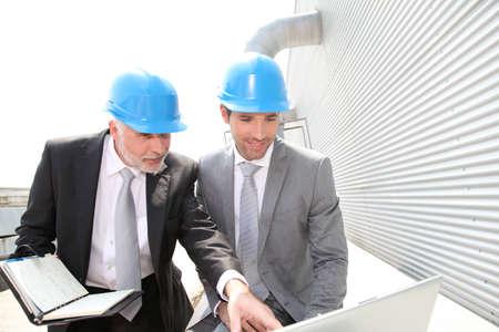 Les partenaires d'affaires travaillant sur le site industriel