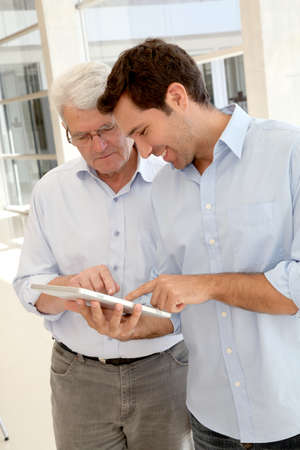 Senior man learning how to use electronic tablet Stock Photo - 9634875
