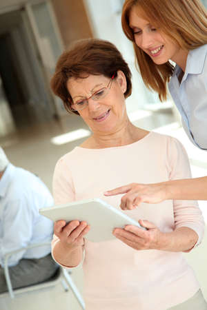 Senior woman learning how to use electronic tablet photo