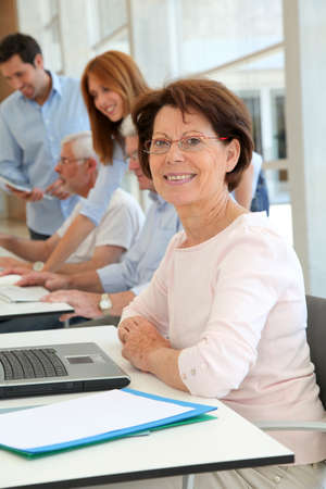 55 years old: Senior woman attending business training Stock Photo