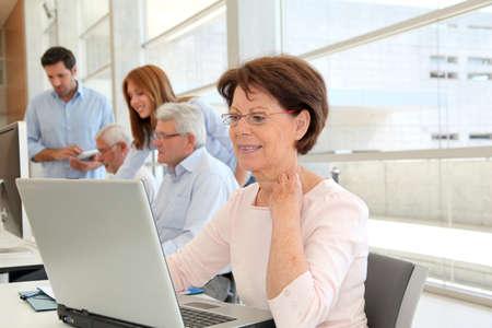 senior ordinateur: Senior femme d'affaires qui suivent une formation
