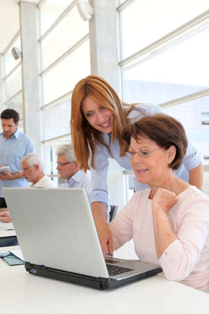 Senior woman with trainer in front of laptop computer photo